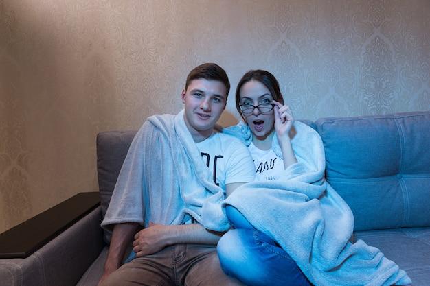 Удивленные молодой мальчик и девочка в очках, прижимаясь друг к другу под одеялом на диване у себя дома, смотрят телевизор, вид спереди в синем сиянии от съемочной площадки