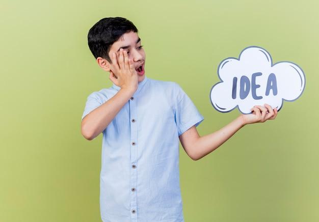 놀란 된 어린 소년 들고 올리브 녹색 벽에 고립 된 얼굴에 손을 유지하는 아이디어 거품을보고