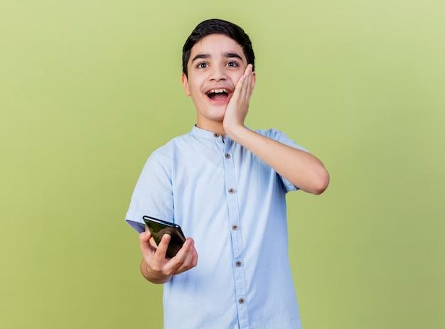 Ragazzo giovane sorpreso che tiene il telefono cellulare guardando la parte anteriore tenendo la mano sul viso isolato sulla parete verde oliva