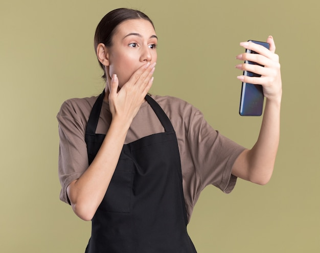 Surprised young brunette barber girl in uniform puts hand on mouth holding and looking at phone isolated on olive green wall with copy space