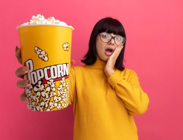 光学メガネで驚いた若いブルネットの白人の女の子は、顔に手を置き、コピースペースでピンクの壁に分離されたポップコーンのバケツを保持します。