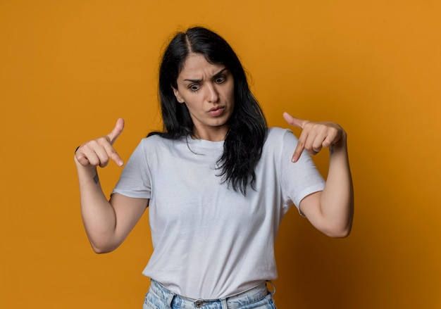 Удивленная молодая брюнетка кавказская девушка указывает вниз, изолированную на оранжевой стене