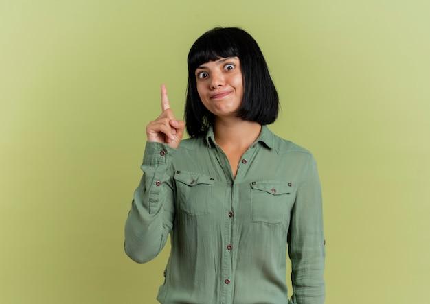 La giovane ragazza caucasica castana sorpresa indica in su isolato su fondo verde oliva con lo spazio della copia