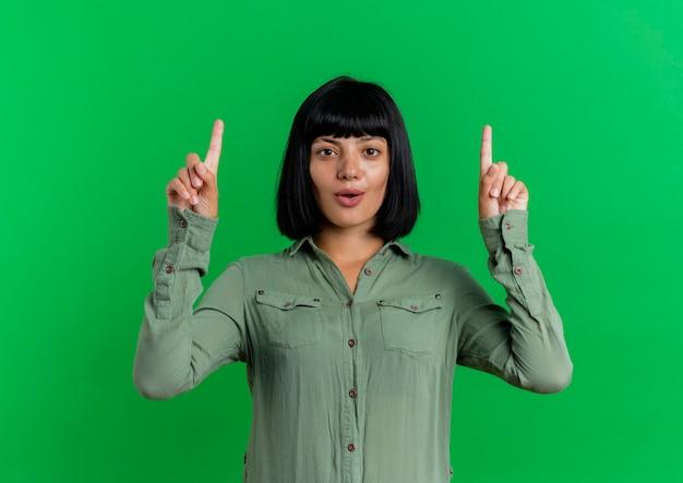 La giovane ragazza caucasica castana sorpresa indica con due mani isolate su priorità bassa verde con lo spazio della copia
