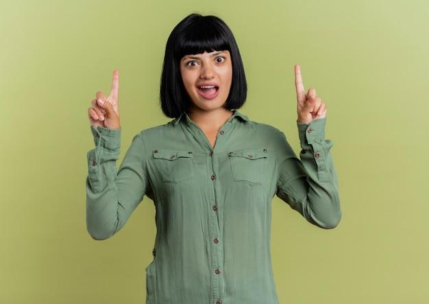 La giovane ragazza caucasica castana sorpresa indica con due mani isolate su fondo verde oliva con lo spazio della copia