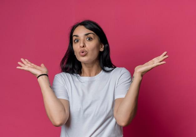 La giovane ragazza caucasica castana sorpresa sta con le mani aperte isolate sulla parete rosa
