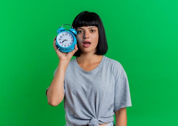 驚いた若いブルネット白人女性は、緑の背景に分離された目覚まし時計を保持します。