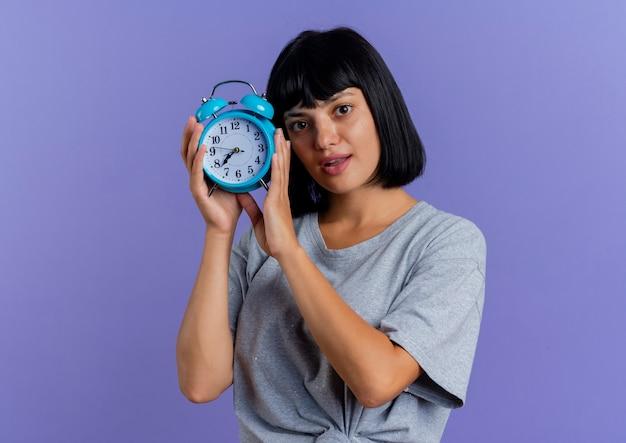 La giovane donna caucasica castana sorpresa tiene la sveglia isolata su fondo viola con lo spazio della copia