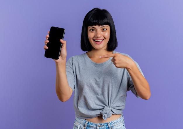 La giovane donna caucasica castana sorpresa tiene e indica il telefono isolato su fondo viola con lo spazio della copia