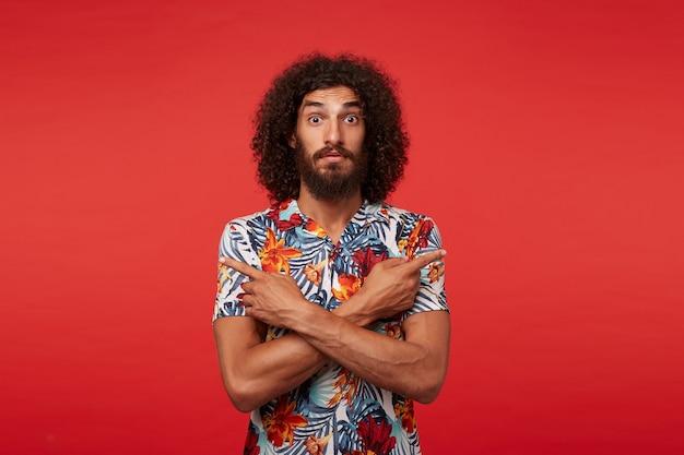 Удивленный молодой брюнет кудрявый мужчина с бородой держит скрещенные руки на груди и смотрит в камеру широко открытыми глазами, стоя на красном фоне в повседневной одежде