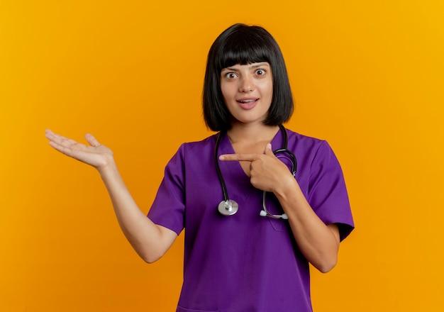 コピースペースとオレンジ色の背景に分離された空の手に聴診器ポイントを持つ制服を着た若いブルネットの女性医師を驚かせ