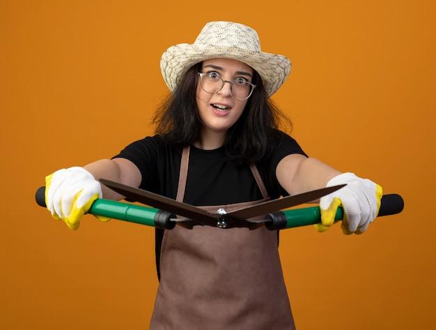Удивленная молодая брюнетка женщина-садовник в оптических очках и в униформе в садовой шляпе и перчатках держит садовые ножницы, изолированные на оранжевой стене