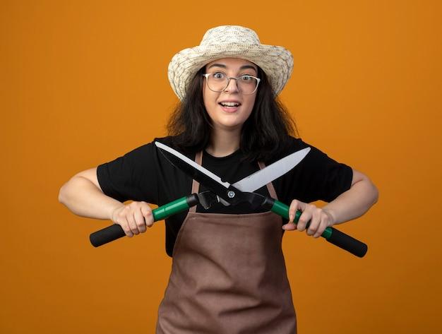 Удивленная молодая брюнетка женщина-садовник в оптических очках и в униформе в садовой шляпе держит садовые ножницы, изолированные на оранжевой стене