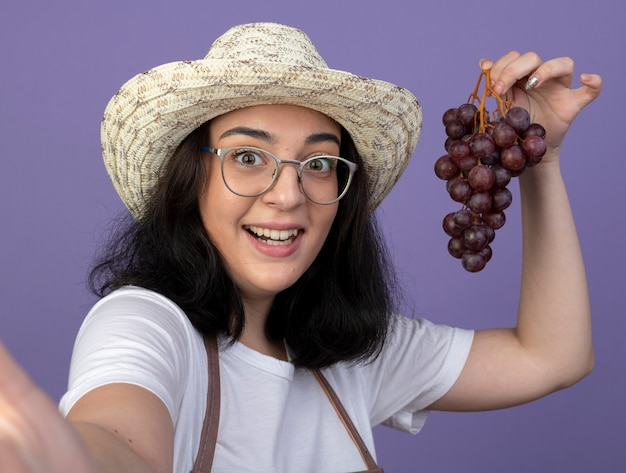 Удивленная молодая брюнетка женщина-садовник в оптических очках и в униформе в садовой шляпе держит виноград, глядя вперед, изолированную на фиолетовой стене