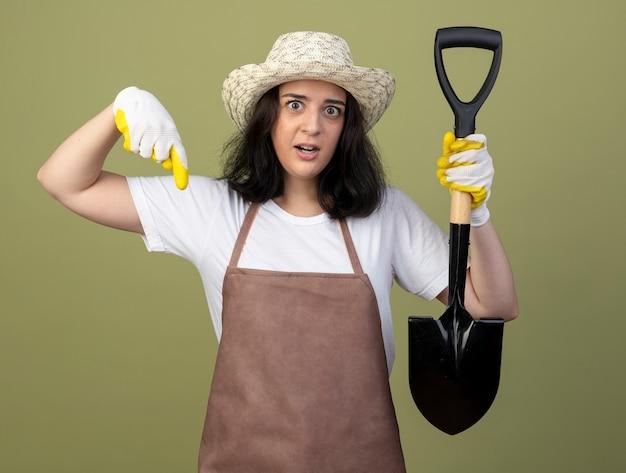 ガーデニング帽子と手袋を身に着けている制服を着た驚いた若いブルネットの女性の庭師は、スペードを保持し、オリーブグリーンの壁に隔離された下を指します