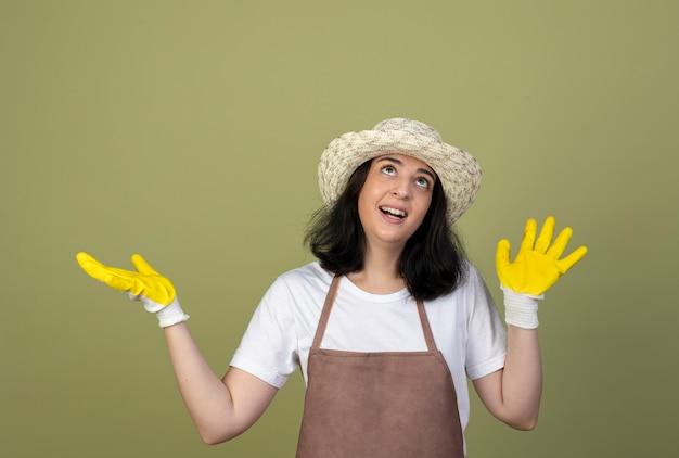 Giardiniere femminile giovane brunetta sorpreso in uniforme che indossa guanti e cappello da giardinaggio sta con le mani alzate che osserva in su isolato sulla parete verde oliva