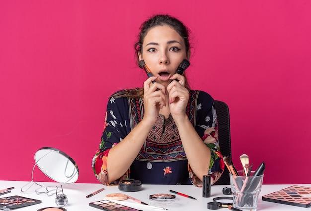Удивленная молодая брюнетка девушка сидит за столом с инструментами для макияжа и держит кисти для макияжа