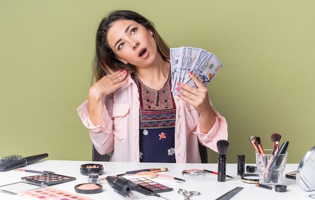 Удивленная молодая брюнетка девушка сидит за столом с инструментами для макияжа, держит деньги и смотрит вверх