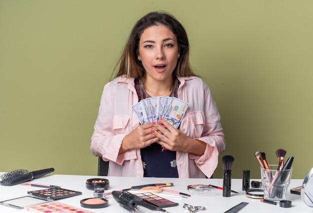 Удивленная молодая брюнетка девушка сидит за столом с инструментами для макияжа и держит деньги