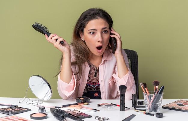 Удивленная молодая брюнетка девушка сидит за столом с инструментами для макияжа, разговаривает по телефону и держит расческу, изолированную на оливково-зеленой стене с копией пространства