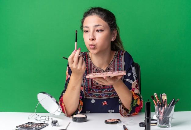 Sorpresa giovane ragazza bruna seduta al tavolo con strumenti per il trucco che tiene la tavolozza dell'ombretto e guarda il pennello per il trucco