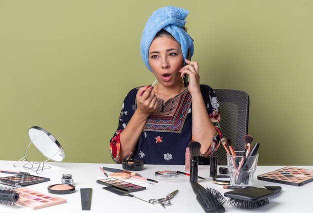 Удивленная молодая брюнетка с обернутыми волосами в полотенце сидит за столом с инструментами для макияжа, разговаривает по телефону и держит блеск для губ