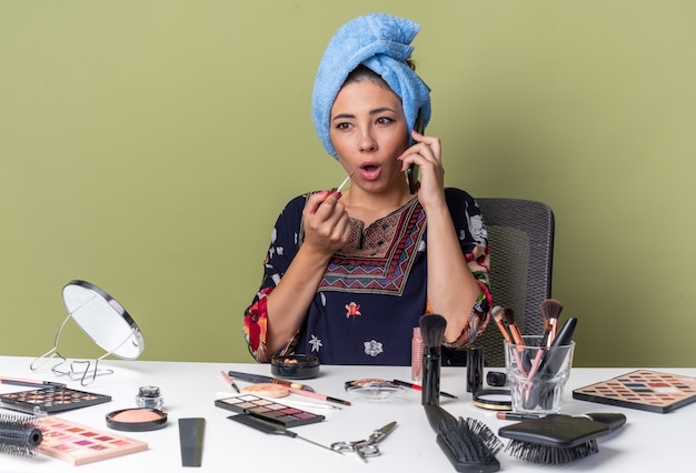 Giovane ragazza castana sorpresa con capelli avvolti in asciugamano che si siede alla tavola con gli strumenti di trucco che parla sul telefono e che tiene lucidalabbra