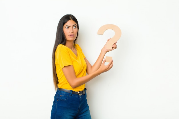 Surprised young brunette woman holding the question mark symbol to form a word or a sentence