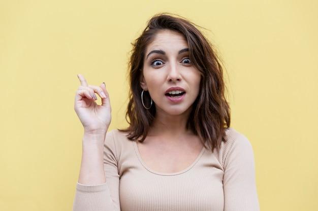 Удивленная молодая женщина брюнет показывая указательный палец вверх. желтая стена.