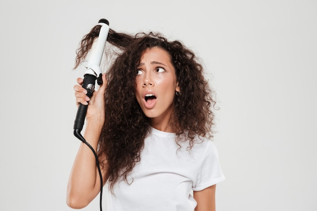 Surprised young brunette woman straighten her hair and looking away