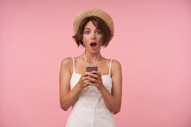 広い目と口で見ている短いヘアカットで驚いた若いブルネットの女性は、予期しないニュースを見つけ、白いサマードレスとカンカン帽でポーズをとる