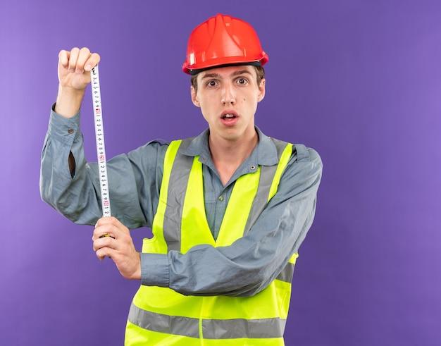줄자를 밖으로 기지개 하는 제복을 입은 놀란된 젊은 건축업자 남자