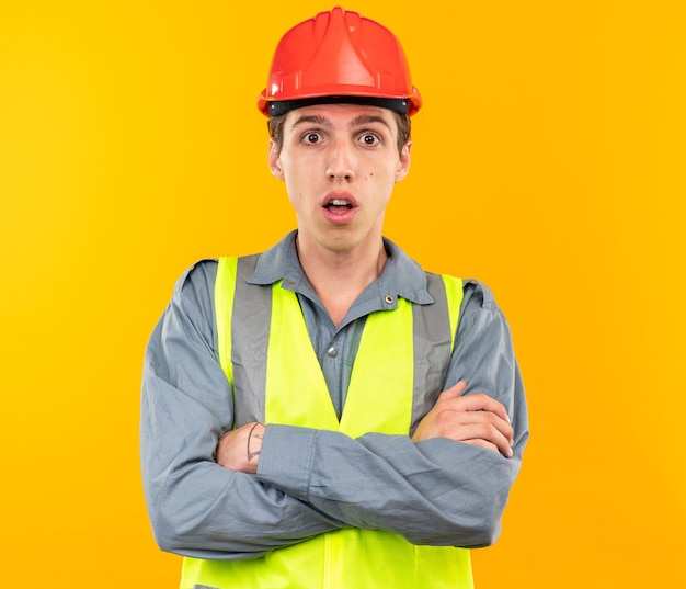 Sorpreso giovane costruttore in uniforme incrociando le mani