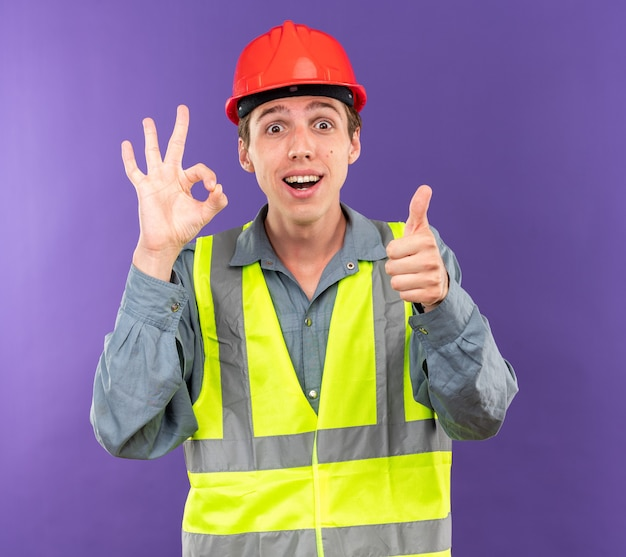Surprised young builder man in uniform showing okay gesture his thumb up