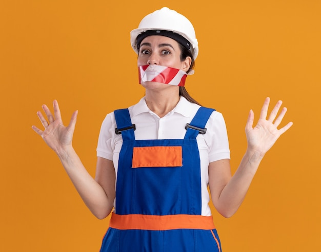 Surprised young builder woman in uniform sealed mouth with duct tape spreading hands isolated on orange wall
