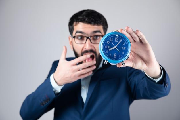 時計を保持している驚いた若いビジネスマン