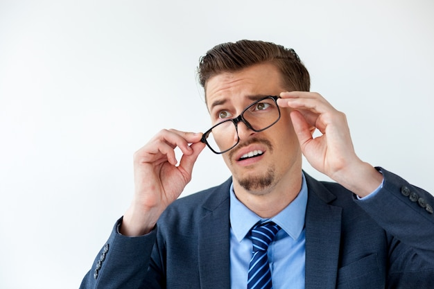 Surprised young businessman putting off glasses