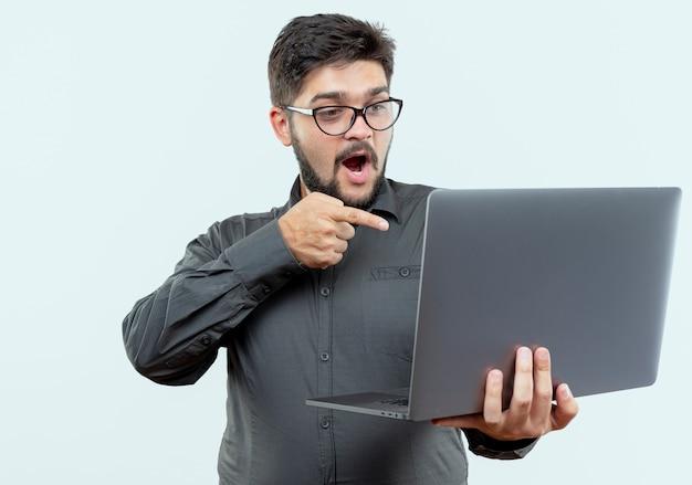 Giovane imprenditore sorpreso che indossa occhiali tenendo e punti al computer portatile isolato su bianco