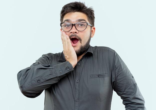 Giovane uomo d'affari sorpreso con gli occhiali che mette la mano sulla guancia isolata su bianco