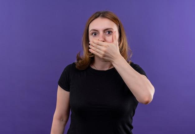 복사 공간이 격리 된 보라색 벽에 손으로 입을 닫는 놀란 젊은 캐주얼 여성