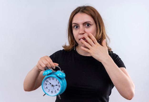 目覚まし時計を保持し、孤立した白い壁に手を口に置いて驚いた若いカジュアルな女性