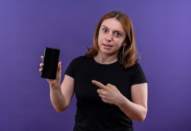 Удивленная молодая случайная женщина держит мобильный телефон и указывает на него на изолированной фиолетовой стене