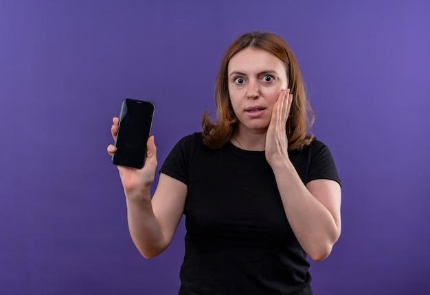 Giovane donna casuale sorpresa che tiene il telefono cellulare e che mette la mano sulla guancia sulla parete viola isolata con lo spazio della copia