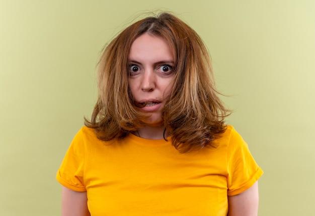Giovane donna casuale sorpresa sulla parete verde isolata