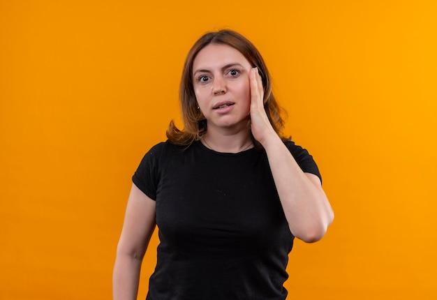 コピースペースのある孤立したオレンジ色の壁に頬に手を置く驚きの若いカジュアルな女性