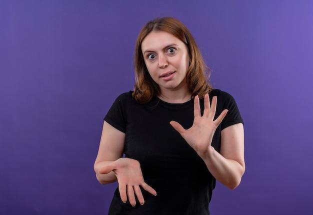 コピースペースと孤立した紫色の壁に空の手を示す驚いた若いカジュアルな女性