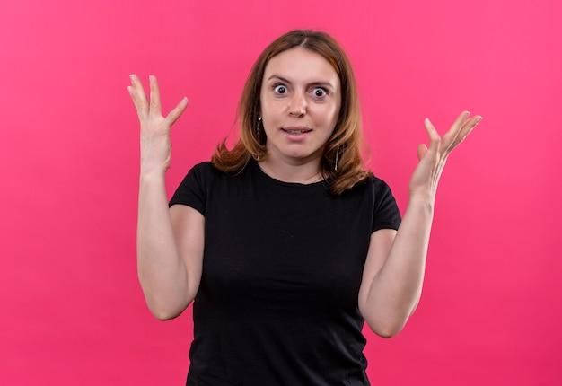 Giovane donna casuale sorpresa con le mani alzate sulla parete rosa isolata
