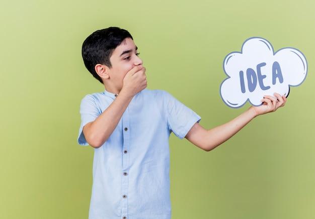 Удивленный молодой кавказский мальчик, держащий и смотрящий на пузырь идеи, держа руку на рту, изолированном на оливково-зеленом фоне с копией пространства