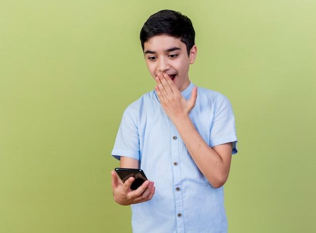 Giovane ragazzo caucasico sorpreso che tiene e che esamina il telefono cellulare che tiene la mano sulla bocca isolata su fondo verde oliva con lo spazio della copia