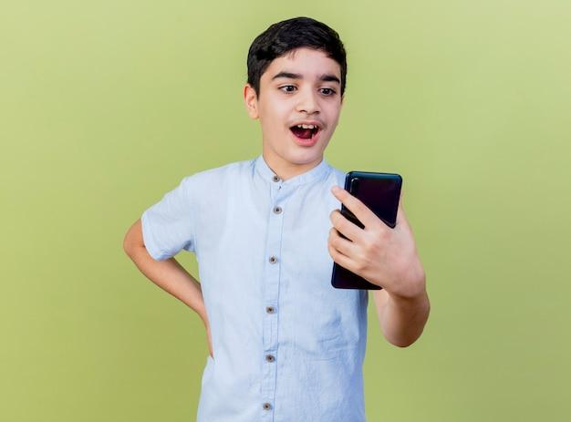 Giovane ragazzo caucasico sorpreso che tiene e che esamina il telefono cellulare che tiene la mano sulla vita isolata su fondo verde oliva con lo spazio della copia